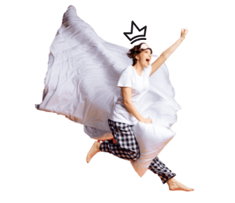 A woman jumping with a pillow and bed sheets.